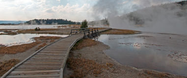 Curved Elevated wooden boardwalk going past Black Warrior Hot Springs and Tangled Creek into Hot Lake in Yellowstone National Park Royalty Free Stock Photo