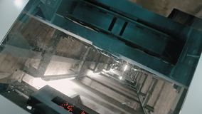 Curved elevator shaft. A downward elevator with a transparent glass top through which the mechanism is visible. The. Reverse can be used to raise up stock video