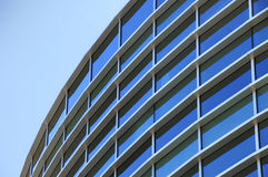 Curved exterior windows of a office building. Curved exterior windows of a commercial office building reflecting a blue sky Stock Images
