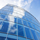 Curved facade of modern glass blue office and clouds Royalty Free Stock Image