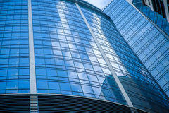 Curved facade of modern glass blue office and sky with clouds reflected Stock Photo