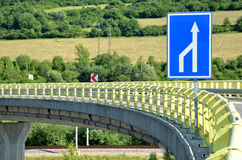 Curved feeder road in countryside, white arrow traffic sign in foreground Stock Image