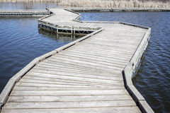 Curved floating walking bridge over a lake. Royalty Free Stock Photography