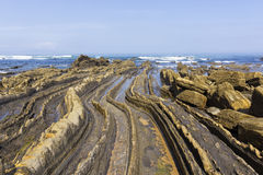 Curved flysch in the shoreline Stock Photos