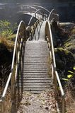 Curved foot bridge over rocks Stock Photography