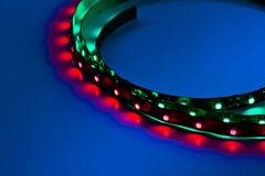 Curved in frame LED Lights. Close up of LED lighting strips illuminated against blue background with very narrow depth of field. Printed circuitry clearly seen royalty free stock images