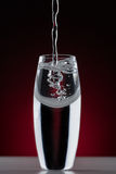 Curved glass with bubbles. Pouring water into a curved glass with bubbles on a dark red background Stock Image