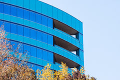 Curved Blue Glass Building and Sky in Fall Royalty Free Stock Photo