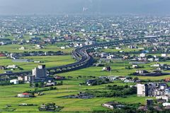 A curved highway through the green rice fields with houses scattered throughout the plain in Yilan, Taiwan. ~ Aerial view of National Freeway No.5, Taipei-Ilan stock image