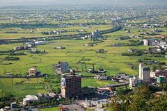 A curved highway through the green rice fields with houses scattered throughout the plain in Yilan, Taiwan. ~ Aerial view of National Freeway No.5, Taipei-Ilan royalty free stock photo