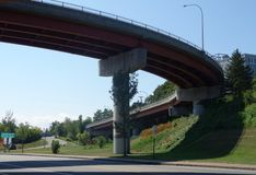 Curved highway overpass, inclined, view from underneath. Over pass road in Portland, Maine, USA, September 5, 2018, and two other roads, many green trees royalty free stock photo