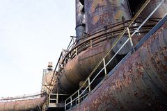 Curved industrial pipes and tubes of old steel mill with heavy patina of rust, copy space. Horizontal aspect stock photography