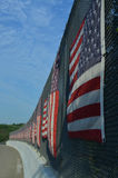 Curved Line of American flags on sunny side of highway overpass fence. Curved line of flags on sunny side of the highway overpass in early morning with a portion Stock Image