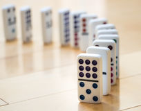 Curved Line of Colorful Dominoes on Wooden Floor Stock Photography