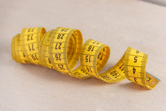 Curved measuring tape. Closeup view of yellow measuring tape. Royalty Free Stock Images