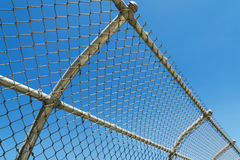 Curved mesh fence. With blue sky Stock Image