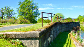 Curved metal railings . Curved metal railings next to canal with shadow Royalty Free Stock Images