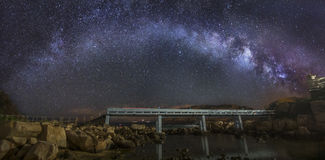 Curved Milky Way over a bridge stock image