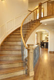 Curved Oak Staircase. All wood curved staircase with hallway and kitchen in view Stock Image