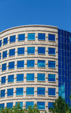 Curved Office with Clouds Reflected in Blue Glass Stock Photo