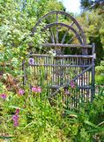 CURVED OLD FASHIONED WOODEN GATE IN GARDEN. This old fashioned crafted wooden gate was placed in a scenic garden of greenery and pink flowers. The top of the Royalty Free Stock Images