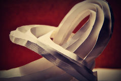 Curved origami form. Folded white origami paper form on a brown background Stock Image