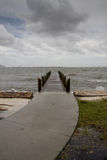 Curved Path to Pier Stormy Afternoon - Vertical. Vertical oriented image of curved sidewalk leading up to a wooden pier on an stormy afternoon with looming dark stock photos