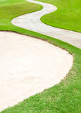 Curved pathway and sand bunker in beautiful green golf cours Royalty Free Stock Photos