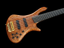 Curved patterned wood bass guitar on black Stock Photos