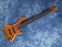 Curved patterned wood bass guitar on blue Royalty Free Stock Photo