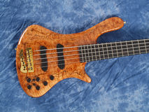 Curved patterned wood bass guitar body stock photos