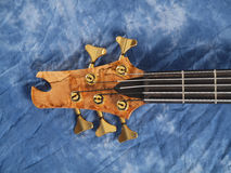 Curved patterned wood bass guitar headstock. On blue muslin Stock Photo