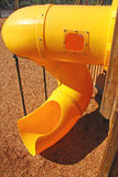 Curved Playground slide. Curvy yellow playground slide in afternoon sun Royalty Free Stock Photo