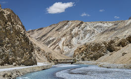 Curved river and little steel bridge in mountains Royalty Free Stock Image