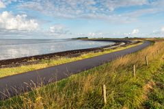 Curved road along the water of an estuary. Curved asphalt road on a dike along the water of a Dutch estuary. It is low tide on a sunny day in the summer season Royalty Free Stock Photography