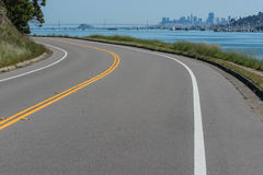 Curved road with double yellow and water Royalty Free Stock Images