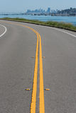 Curved road with double yellow and water Royalty Free Stock Image