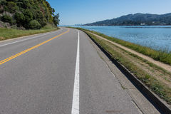 Curved road with double yellow and water Royalty Free Stock Photos