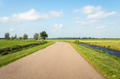 Curved road in a flat polder landscape. Curved road in a flat Dutch polder landscape in the Alblasserwaard, South Holland. Cumulus clouds are in the blue sky stock photography