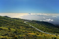 Curved Road on Hill Above Clouds Stock Image
