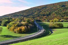 Curved road on hillside with green covered filed and fall foliage royalty free stock image