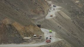 Curved road on the side of a  mountain. A dolly, wide shot of a curved road situated on the side of a mountain, and a series of vehicles passing through a tunnel stock video footage