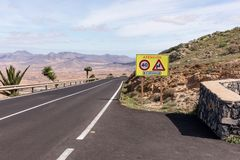 Curved road with sign Attention in Fuerteventura. Canary Islands. Spain royalty free stock photos