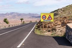 Curved road with sign Attention in Fuerteventura. Canary Islands. Spain stock photos