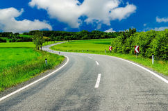 Curved road in a summer landscape Stock Photos