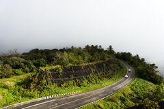 Curved road to Doi Inthanon National Park, Chiangmai, Thailand in misty stock image