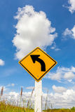 Curved road traffic sign in farmland with cloudy blue sky backgr Royalty Free Stock Image