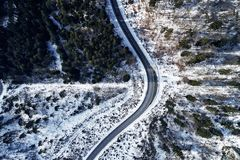Curved road in winter mountain landscape. Aerial view of forest and trees with a winding street surrounded by snow. Curved road in winter mountain landscape stock photo