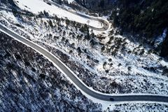Curved road in winter mountain landscape. Aerial view of forest and trees with a winding street surrounded by snow. Curved road in winter mountain landscape royalty free stock images