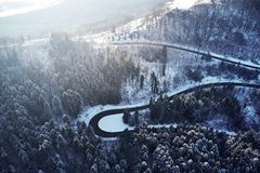 Curved road in winter mountain landscape. Aerial view of forest and trees with a winding street surrounded by snow. Curved road in winter mountain landscape royalty free stock photography